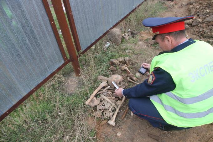 Криминалист полиции фотографирует кости обнаруженные в районе набережной