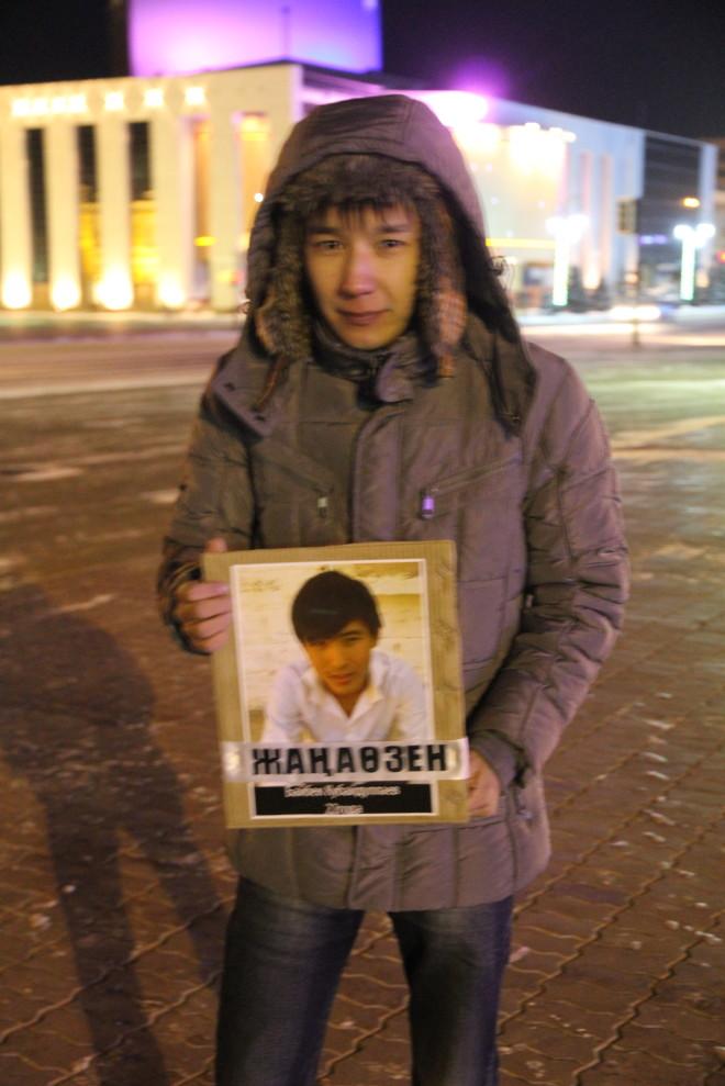 22-летний Азамат Муханов с фотографией одного из погибших в Жанаозене