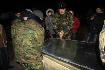 На фото: заместитель командира военной части 6505 Ануар Укубаев помогает военным выгрузить тело погибшего солдата Бекжана Бауыржанова.