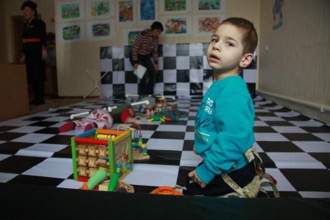 """Трехлетний Наиль научился сидеть, но - неправильно. Поза """"лягушки"""" искривила ноги. Приспособление """"антисид"""" не позволяет ему сесть в любимую позу и корректирует ноги."""