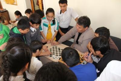 Данияр Жумагалиев (в центре) во время партии в шашки с Аманбеком Дияровым.
