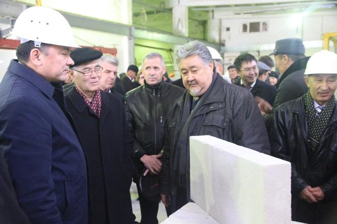 """Председатель правления АО """"ЗККСМ"""" Мухаммеджан Кенжигулов (в центре) демонстрирует акиму области образец блока из ячеистого бетона"""