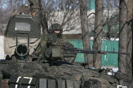A fighter with the separatist self-proclaimed Donetsk People's Republic Army sits atop a tank at a checkpoint along a road from the town of Vuhlehirsk to Debaltseve in Ukraine