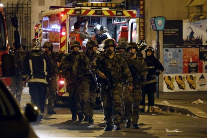 TOPSHOTS Soldiers walk in front of an ambulance as rescue workers evacuate victims near La Belle Equipe, rue de Charonne, at the site of an attack on Paris on November 14, 2015 after a series of gun attacks occurred across Paris as well as explosions outside the national stadium where France was hosting Germany. More than 100 people were killed in a mass hostage-taking at a Paris concert hall and many more were feared dead in a series of bombings and shootings, as France declared a national state of emergency.  AFP PHOTO / PIERRE CONSTANTPIERRE CONSTANT/AFP/Getty Images