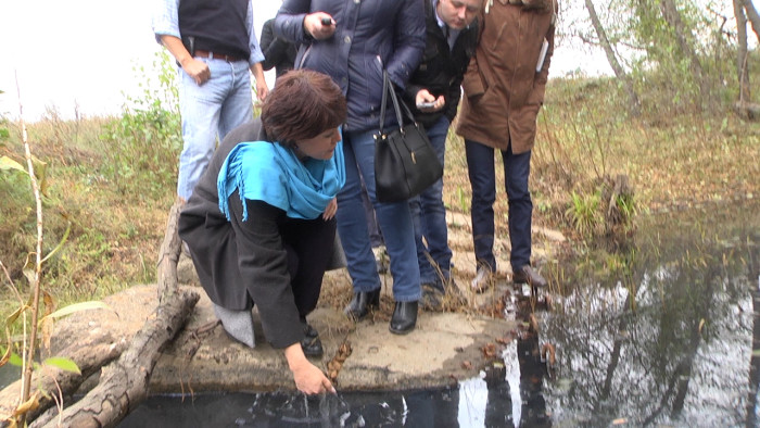 Руководитель управления по защите прав потребителей Альфия Хасенова проверяет состояние реки в присутствии журналистов.  20 октября 2016 года.