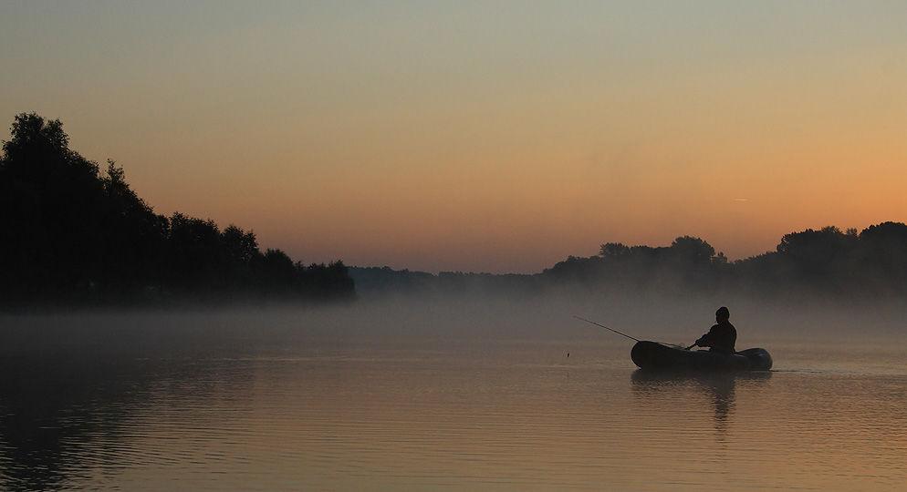 Лодка на воде с рыбаком